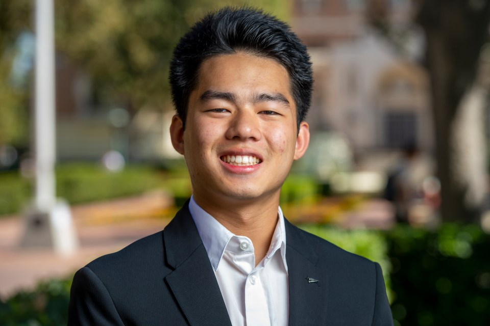 USC First-year student Tony Ouyang photographed standing outside in the USC courtyard, looking straight into the camera and smiling. He plans to work hard, graduate, explore venture opportunities, and give back to his family who helped him get to LA.
