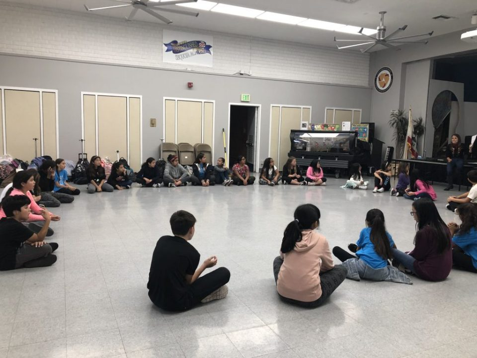 A class room of children all sitting in a circle for Jackie's dance outreach program.