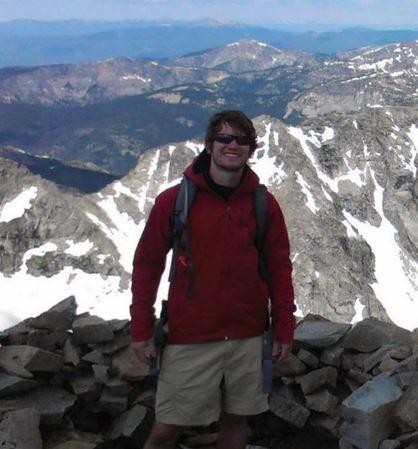 UMD alumni, Dan Powell, hiking up a mountain