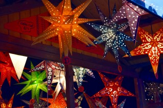 Colorful paper star lanterns illuminate this stall.