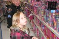 Above Officer Lisa Gavahan helped Kasey Andrews (left) and Marjorie Soto (right) pick out items for their family during Genoa City Police Department's Shop with a Hero Program. Officer Mike Sireno (right) helped fourth grader, Cerisa Kumm pick out items in the Barbie aisle during Genoa City Police Depart-ment's Shop with a Hero Program.