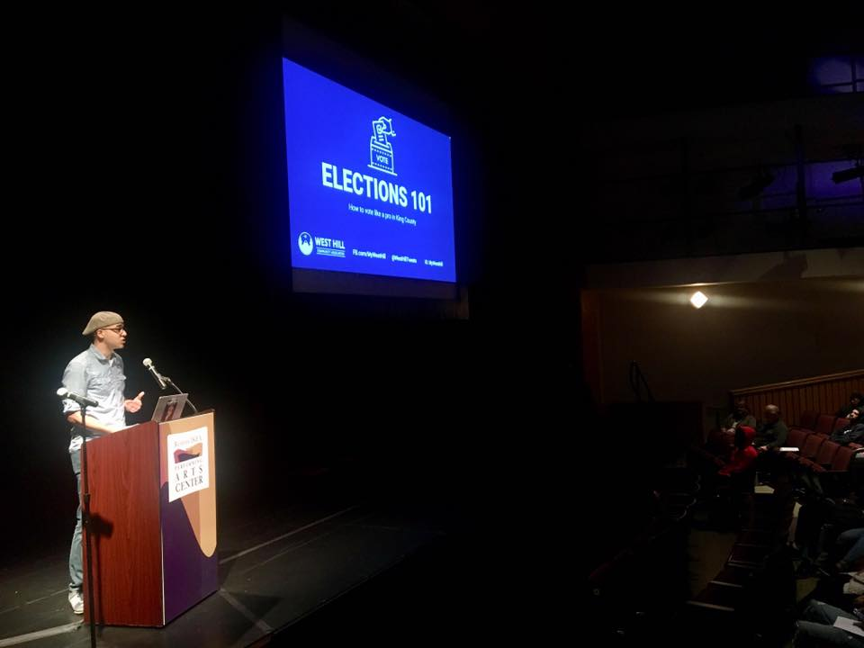 WHCA Board President Jeremy Williams speaking to Renton High School students about voter education in the Ikea Performing Arts Center, October 2019