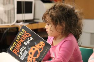 Young child reads book at REACH Center of Hope.