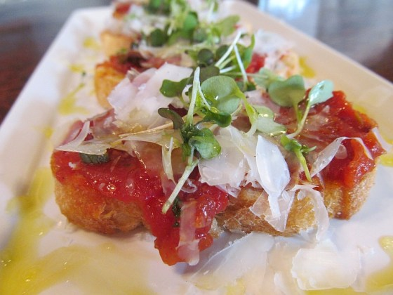 Tapas of tomato and green olives topped with Manchego cheese