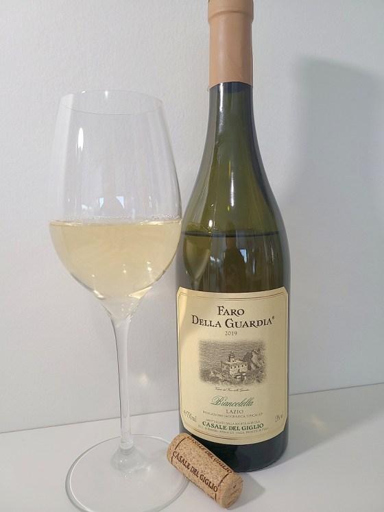 Casale del Giglio Faro Della Guardia Biancolella di Ponza Lazio IGT 2019 with wine in glass