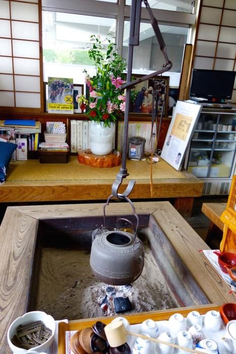 Der Teekessel hängt über einer offenen Feuerstelle.
