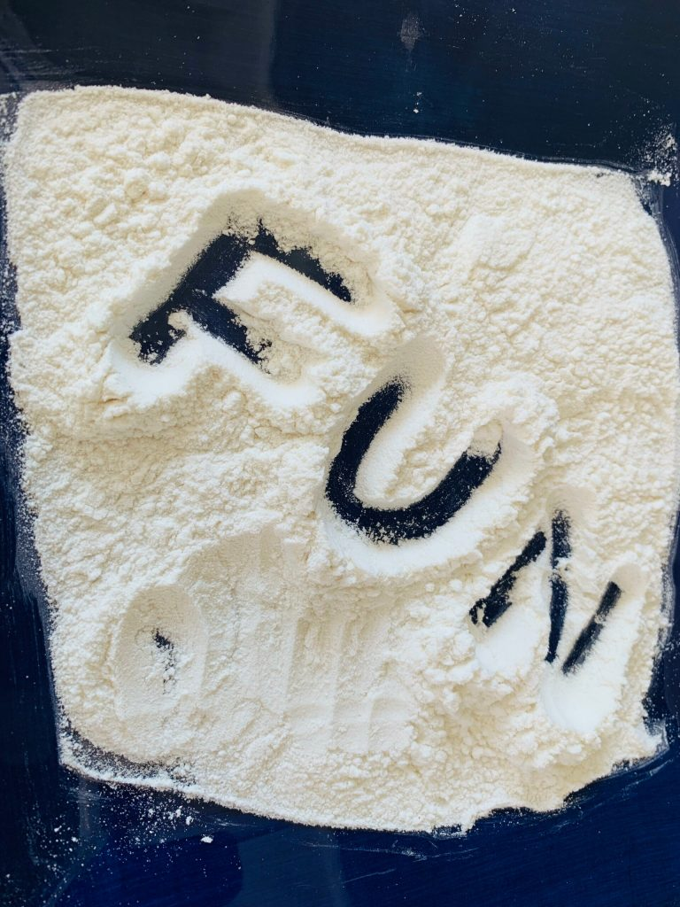 practice spelling words by tracing them in flour