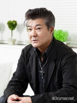 Das Bild zeigt den Entwickler des Spiels Trials of Mana Koishi Ishii. Er hat schwarze Haare mit silbernen Stähnen, trägt ein schwarzes Hemd und eine Kette mit einem Kreuz um den Hals.