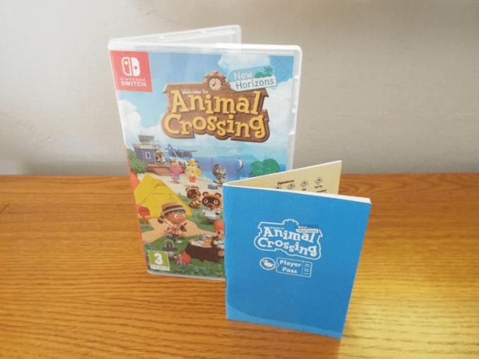 Das Bild zeigt das Manual zu Animal Crossing: New Horizons stehend, im Hintergund das Spiel in Packung.