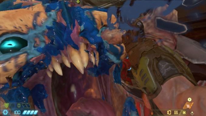 """Auf diesem Bild des Spiels """"Doom Eternal"""" ist ein großes Dämonengesicht (blau blutend) zu sehen."""