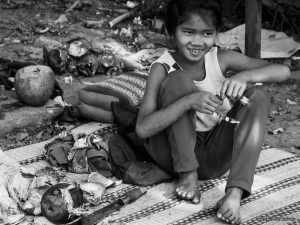 A young girl processing coconuts using a machete knife