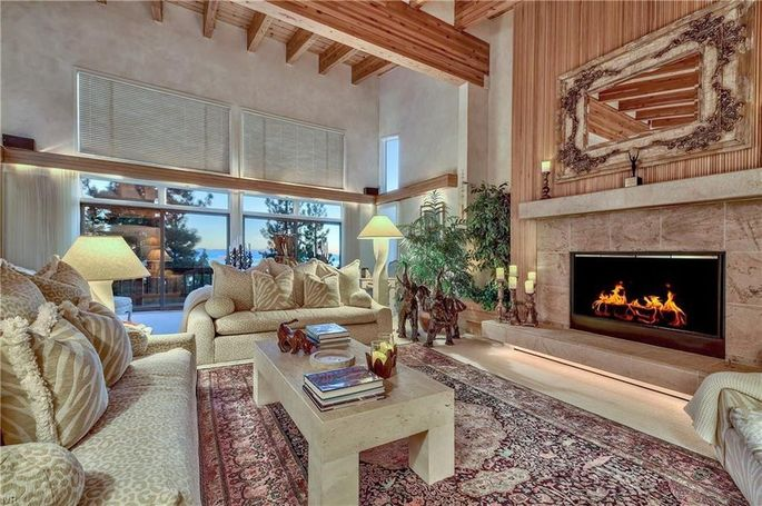 Living room with beamed ceiling and stone fireplace