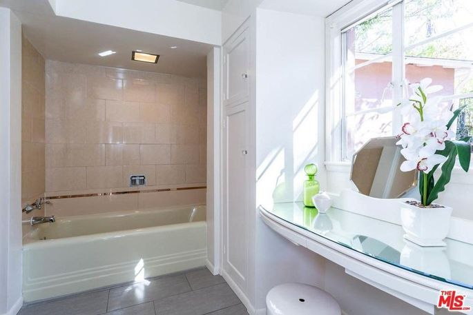 Bathroom with original pastel-colored tile and built-in dressing table