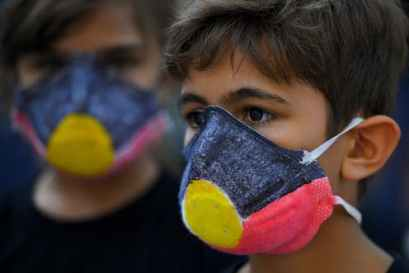 two Aboriginal children wearing COVID-19 face mask painted with Indigenous flag.