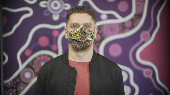 Aaron Simon standing against wall painted with Aboriginal art, wearing an Aboriginal art design face mask