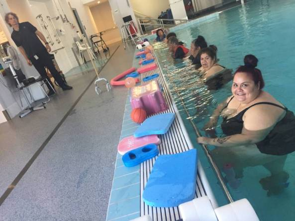 row of Aboriginal women in a pool holding on to the side