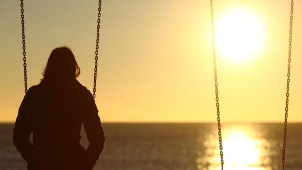 back view of teenage girl at dusk sitting on a swing looking out to sea
