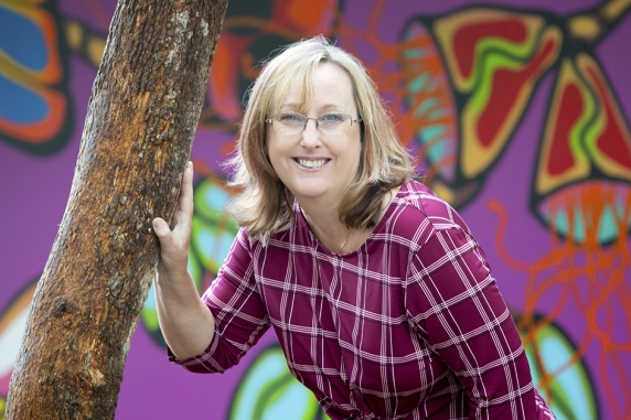 Dr Belinda Davison with hand against tree trunk and wall of Aboriginal art in the background