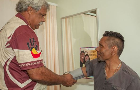 Aboriginal health worker taking blood pressure of Aboriginal man