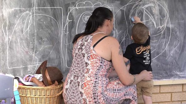 mother watching small child as he draws on chalkboard