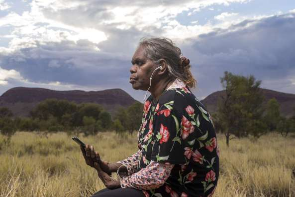 Aboriginal woman on Country listening to podcast