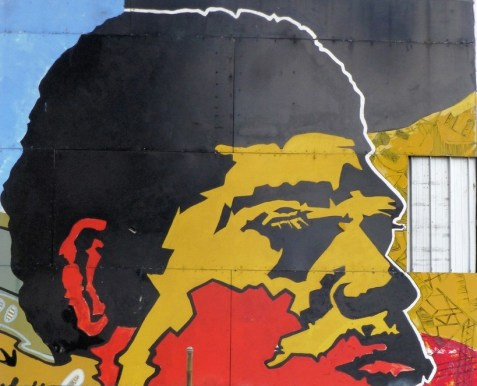 painting of Aboriginal man's head on exterior wall in red yellow & black