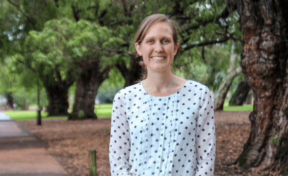 portrait of Associate Professor Asha Bowen standing outside on path with trees in the background