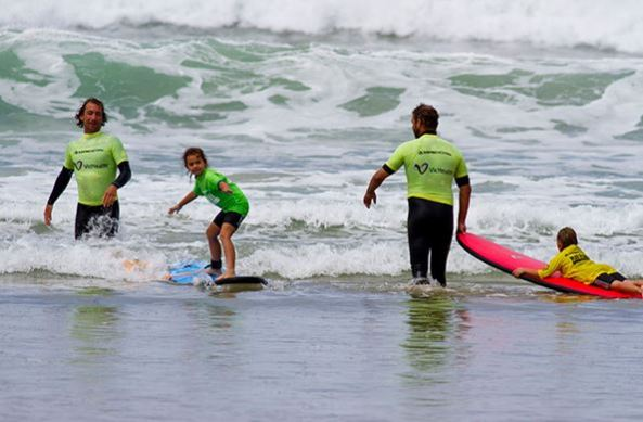 two male adults and two Aboriginal children surfing