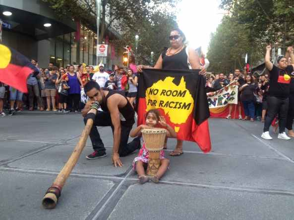 street march, lady with flag Aboriginal colours, words no room for racism inside yellow map of Aust, against black top and red lower half of flag, young Aboriginal girl with drum