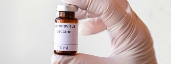 gloved hand holding vial with words Coronavirus vaccine 10 ml