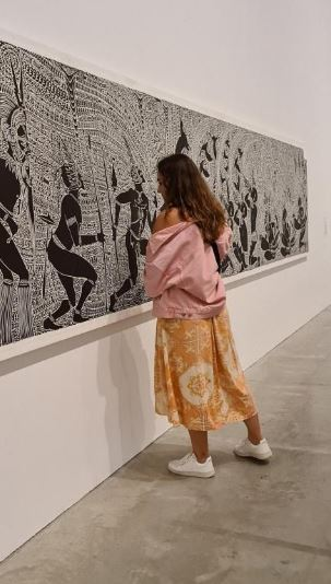 Aboriginal woman looking at Aboriginal art in an art gallery