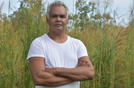 Katherine Indigenous advocate & Gurindji man Kamahi-Djordon King in white t-shirt standing in bushland with head height green grasses, armed folded