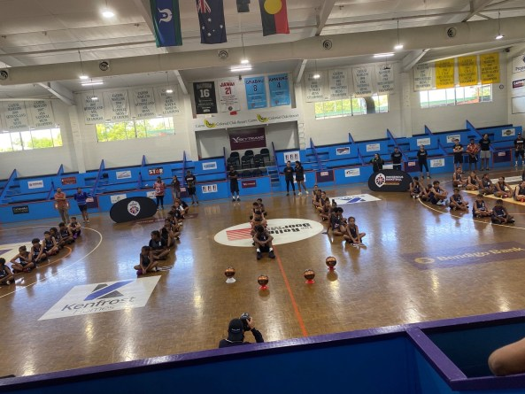 Far North Queensland teams sitting in rows on basketball court at opening ceremony of Indigenous Community Basketball League