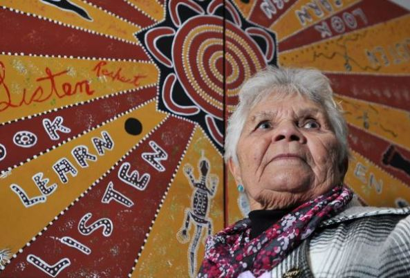 Wiradjuri Elder Aunty Isabel Reid standing against Aboriginal art with words look, learn, listen, respect