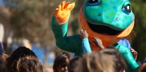 person dressed as Milp the trachoma goanna at AFL game in Alice Springs surrounded by Aboriginal children