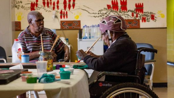 two Aboriginal men in an aged-care facility art room, one in a wheelchair painting