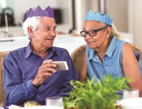 elderly Aboriginal man and Aboriginal woman wearing paper party hats sitting at table looking at a mobile phone screen