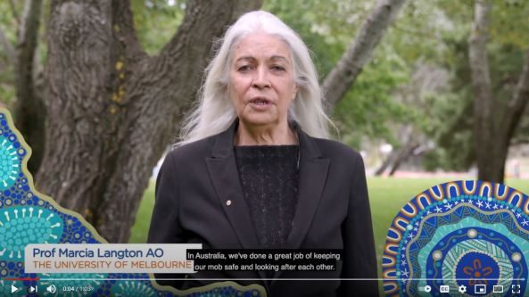 snapshot of Professor Marica Langton AO The Uni of Melbourne video for DoH on COVID-19 importance, standing in park with trees in background