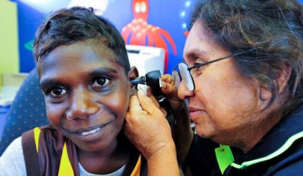 Aboriginal Health Worker examining ear of Aboriginal youth