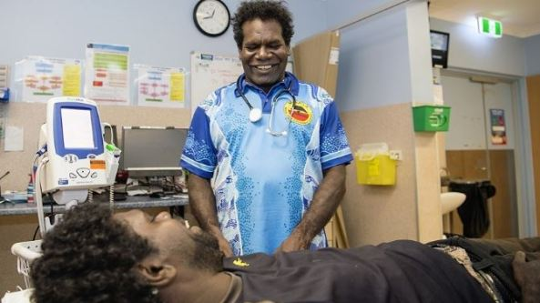 Aboriginal Health Worker smiling at Aboriginal man lying on examination bed in a clinic