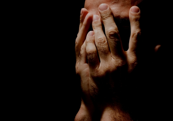 face covered with hands, black background, low light