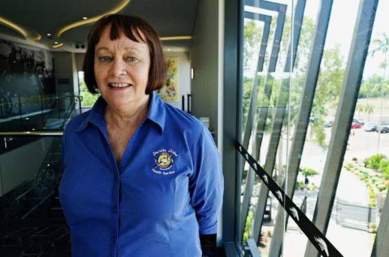 Danila Dilba CEO Olga Havnen in blue Danila Dilba logo shirt stanind inside an office building near a very large glass window
