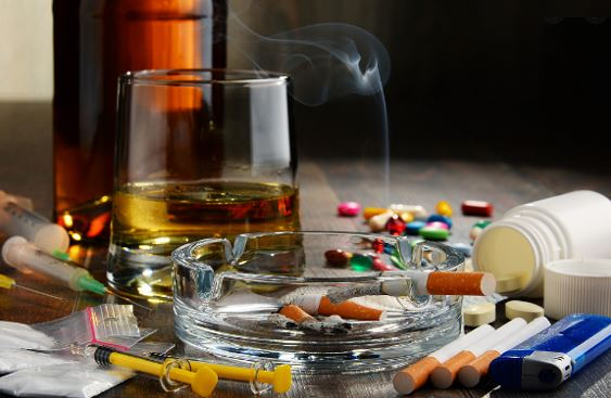 table with cigarettes, one alight with smote in ashtray, lighter, pills, bottle of alcohol, glass with spirits, packets of white powder