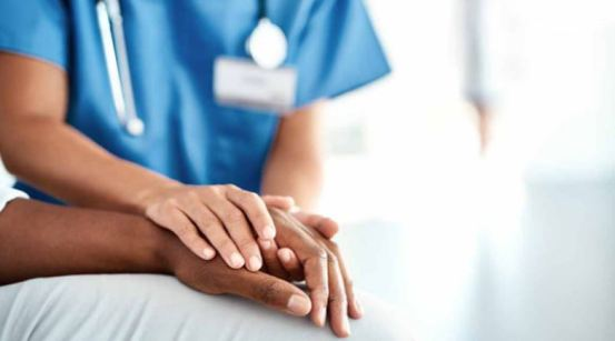 torso of healthcare professional with blue scrubs & stethoscope with hands over patient's hand