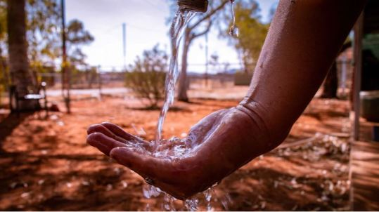 water from tap flowing into Aboriginal person's hand, background is outback setting