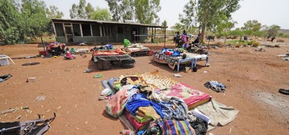 remote Aboriginal community with multiple beds in the open outside a dwelling