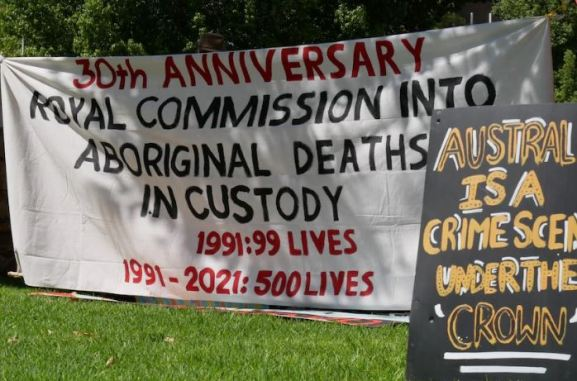 white banner with text in red '30th anniversary' text in black 'roayl commission into Aboriginal deaths in cutody' red text '1991:99 lives; 1991-2021: 500 lives' yeallow text on black separate placard ' Australia is a crime scene under the crown'