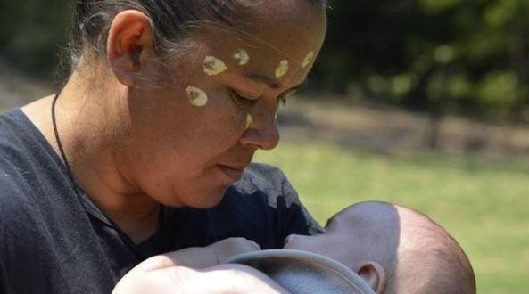 Midwife Melanie Briggs holds newborn Talekai during a special cultural ceremony
