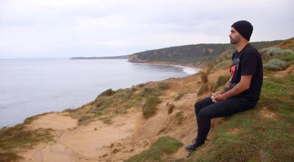 young Aboriginal man sitting on a headland looking out to sea