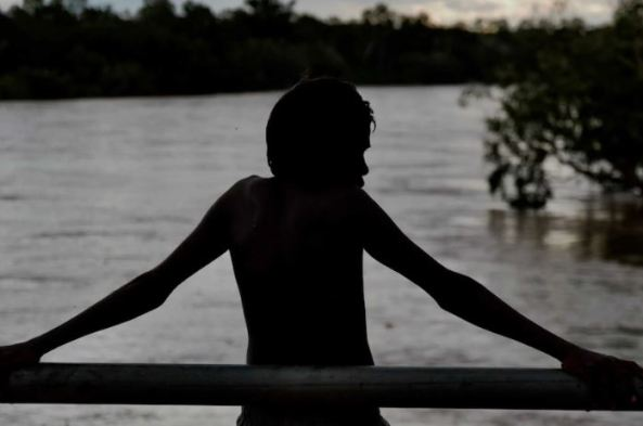 back of child leaning against outside of railing arms outstretched on the railing over-looking a riven, image in black & grey